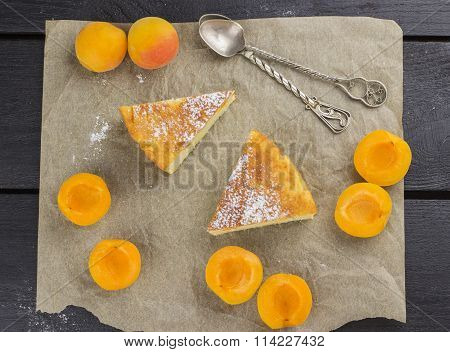 Slices Of Cottage Cheese Pie With Apricots And Icing Sugar On A Brown Wooden Background. Top View