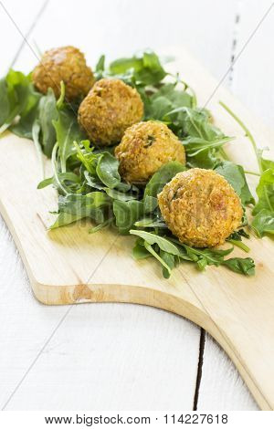 Falafel From Chick-pea On A Wooden Board With Arugula