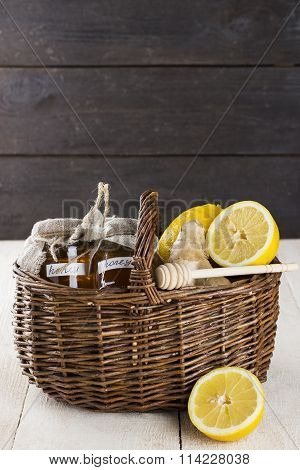 Lemon, Ginger, Honey In Wattled Basket On A Wooden Background