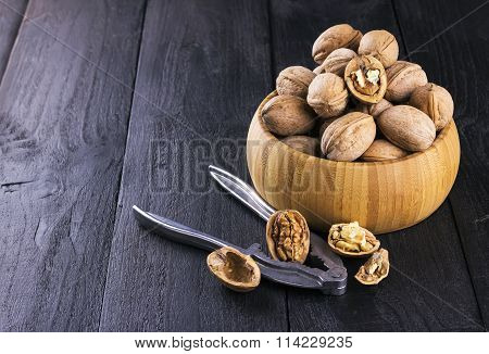 Walnut Kernels And Whole Walnuts On Wooden Background