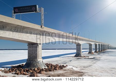 Confederation Bridge linking New Brunswick and Prince Edward Island in winter with lens flare..