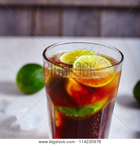 Cuba Libre cocktail on wood background