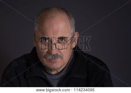 Thoughtful Caucasian man against dark background
