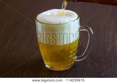 pouring beer from bottle into mug at bar