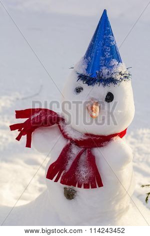 winter landscape background snegovichok in a bright scarf and cap on snow