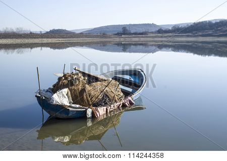 Lonely Fishing Boat In Lake With Reflection