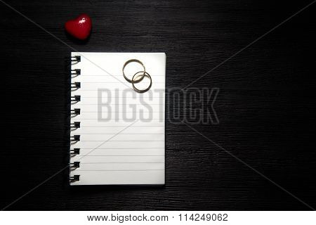 Blank Notebook With Heart And Wedding Rings On Black Background