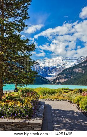 The picturesque promenade on the glacial Lake Louise. The emerald waters of the lake surrounded by mountains, glaciers and pine forests. Banff National Park, Rocky Mountains, Canada