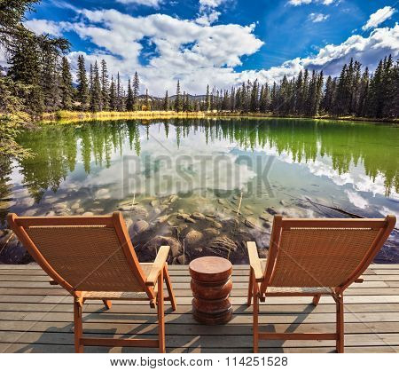 Two wooden deckchairs for tourists before round shallow lake. Autumn day in Jasper  National Park in the Rocky Mountains of Canada