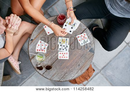 Three Young Friends Playing Cards At Cafe