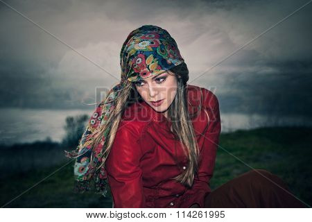 young blue eyes blonde woman in gypsy style fashion, outdoor windy day