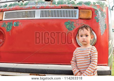 baby boy  standing in front of old mini van retro style