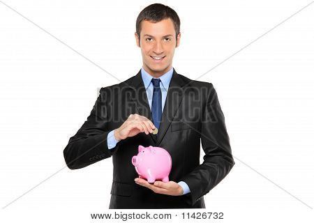 Businessman Putting A Coin Into A Piggy Bank