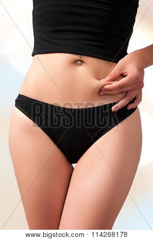 Woman`s slim figure in black underwear. Holding abdomen fat, isolated with work path.