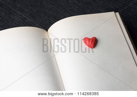 Book about love. Concept of Valentines Day. Red decorative heart on a book page