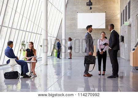 Interior Of Busy Office Foyer Area With Businesspeople