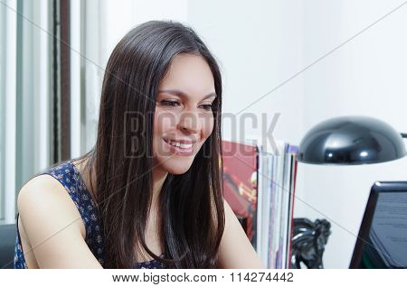 Hispanic brunette office woman sitting by desk and working on computer with positive attitude smilin
