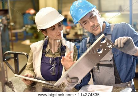 Metallurgy workers in workshop using digital tablet