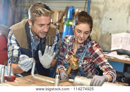 Metal craftsman teaching know-how to young woman