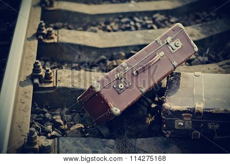 Old Vintage Suitcases Forgotten Lie On Railway Rails.