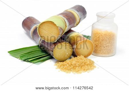 Sugarcane with leaves and granulated brown sugar on white background.