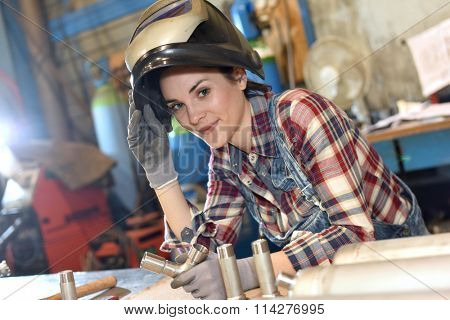 Woman with protective mask in metallurgy workshop