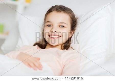 happy smiling girl lying awake in bed at home