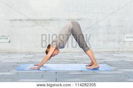 woman making yoga dog pose on mat