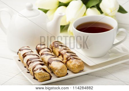 Eclairs and cup of tea on wooden table.
