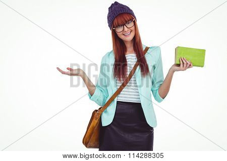 Smiling hipster woman with bag and book against white background