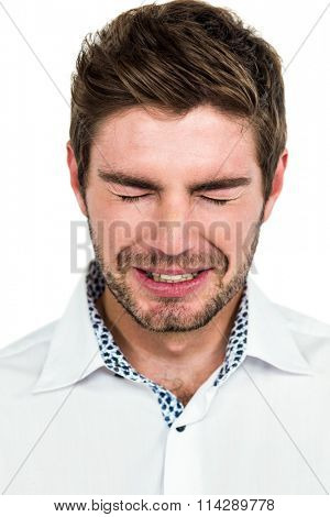 Close-up of crying man standing on white background