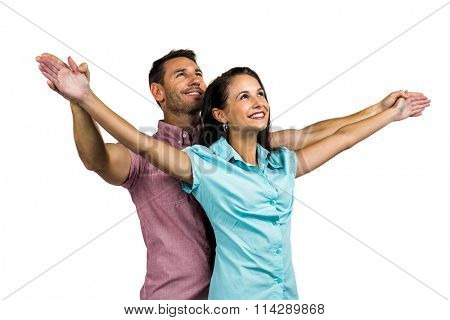 Cheerful couple with arms outstretched on white background