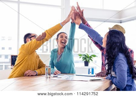 Cheerful business team doing high five while sitting in creative office