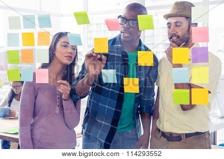 Creative business people discussing over adhesive notes at office