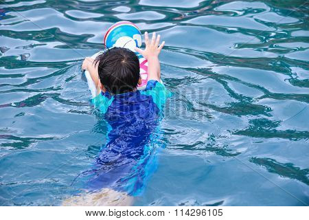 Back View Of Asian Boy With Kick Board And Ball In Pool. Outdoor.