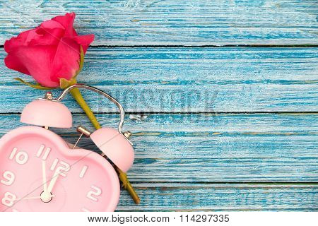 Pink Rose And Pink Heart Watch On The Blue Wooden Background