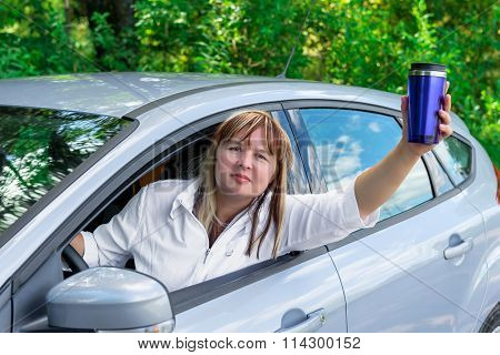 Mature Woman With A Drink Looks Out The Car Window While Driving