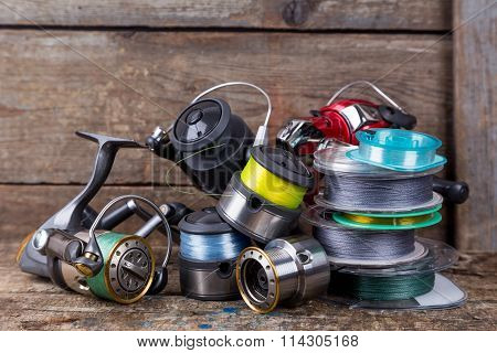 Fishing Reels And Spoole With Line On Wooden Background
