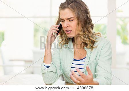 Frowning woman having phone call at home