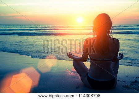 Yoga silhouette. Fitness and healthy lifestyle. Meditation girl on the background of the stunning sea and sunset.