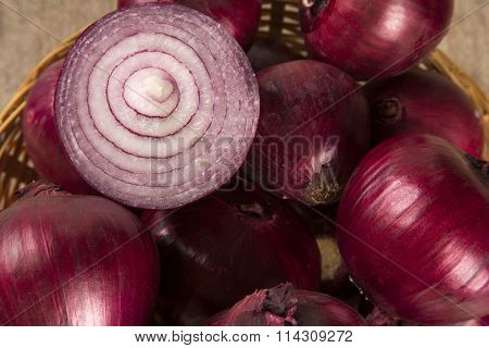 Red Onions In A Basket And A Cut Red Onion Over A Table.