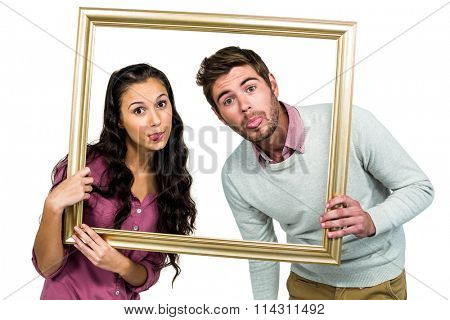 Couple sticking out tongue while holding picture frame on white background