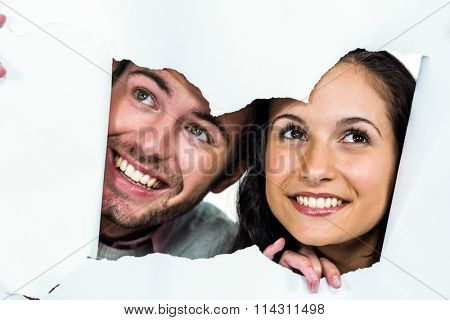 Close-up of smiling couple peeking out torn paper while looking away