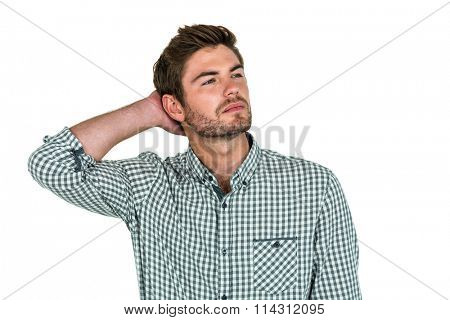 Thoughtful man with hand behind head on white screen