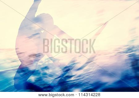 Double exposure of a surfer surfing in the ocean. Summer time colors