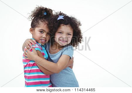 Cute girls hugging and looking at camera on white screen