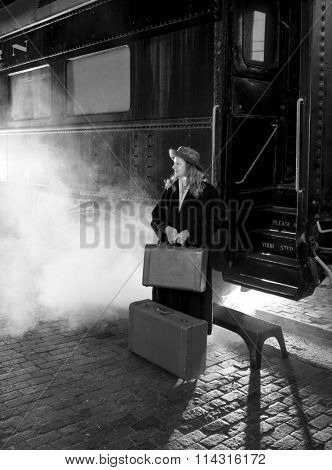 Woman in 1950s clothing leaving on steam train, black and white.