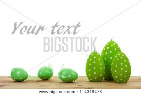 Easter decoration- green candles in the shape of egg and decorative eggs isolated.