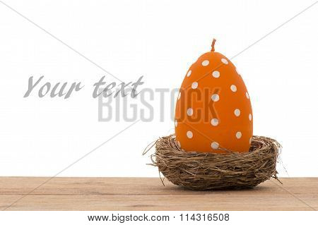 Easter decoration -orange candle in the shape of egg in the nest.