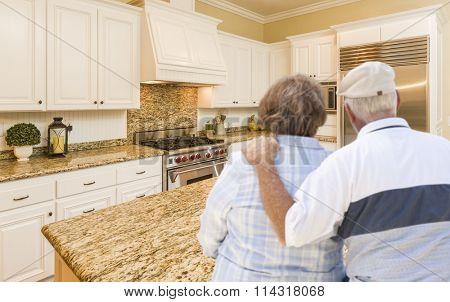 Happy Senior Couple Looking Over Beautiful Custom Kitchen Design.